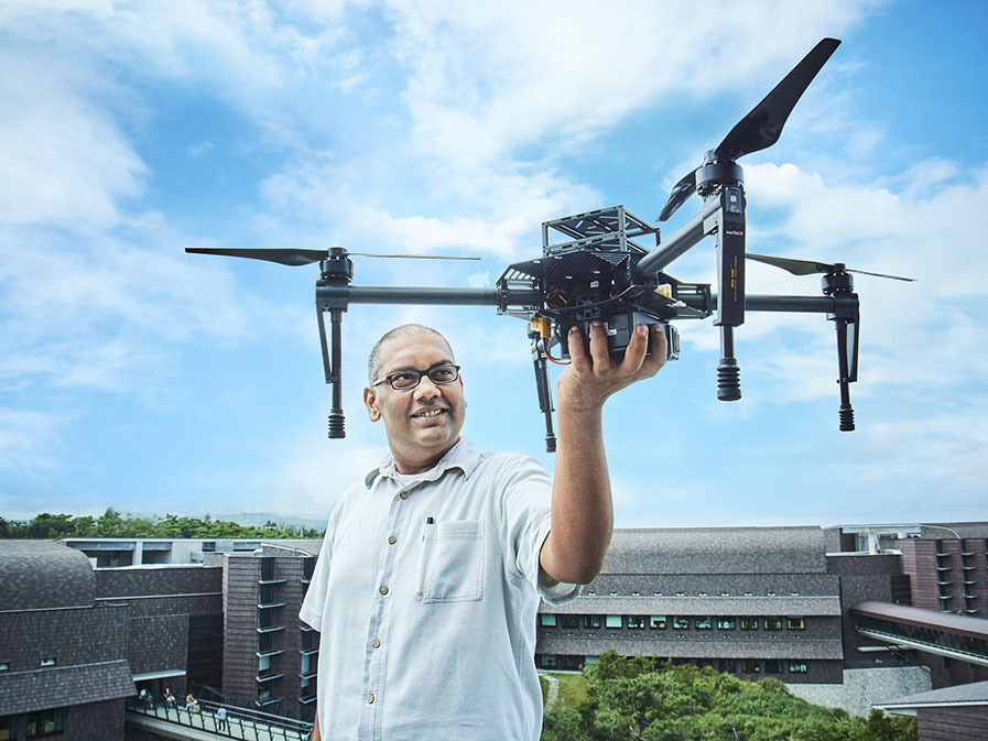 An indian man stands on the roof of a laboratory with the blue sky behind him, holding a drone.